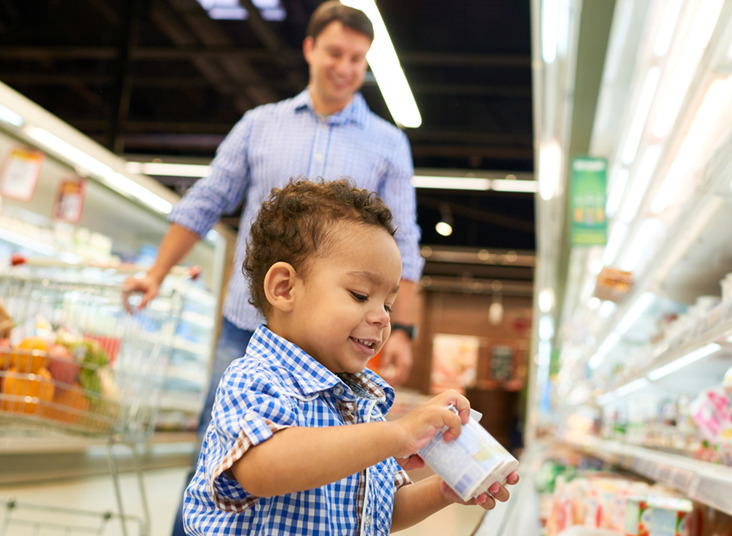 Little toddler boy happily picks up yogurt from the supermarket aisle as his father watches him from behind and smiles