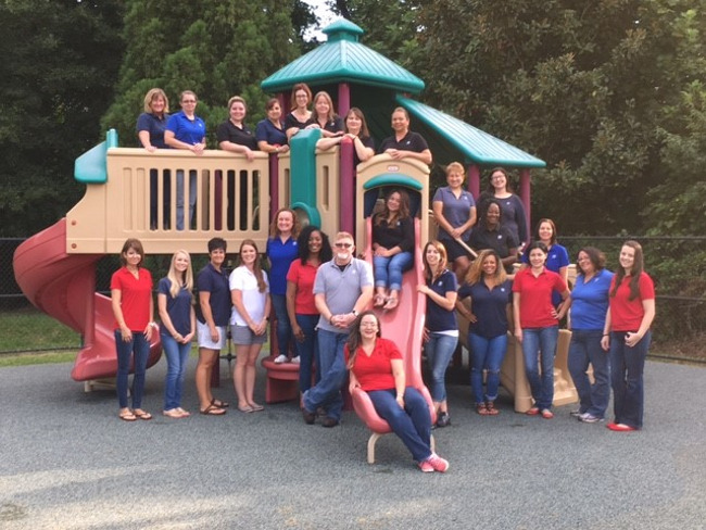 Primrose school of North Raleigh staff pose for a picture on the school Jungle gym