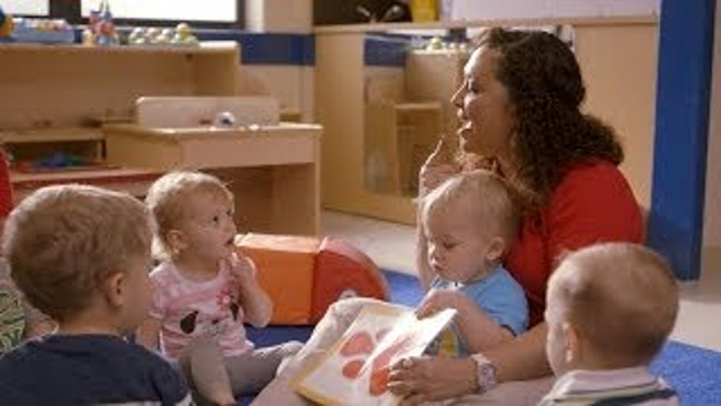 Primrose teacher reads to her toddler students by stressing on her pronunciation