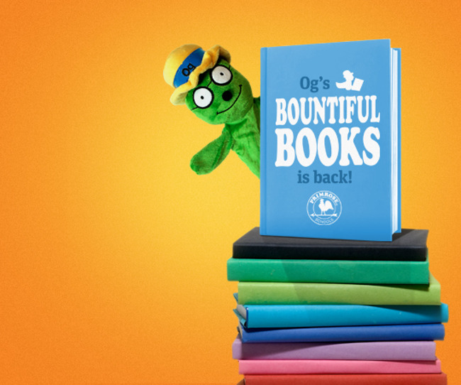 """Og the Bookworm puppet sits on top of a pile of books that read """"Og's Bountiful Books is back"""""""