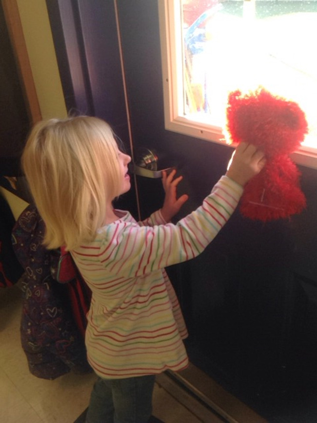 Little girl holds up the Benjamin the bear puppet to the window