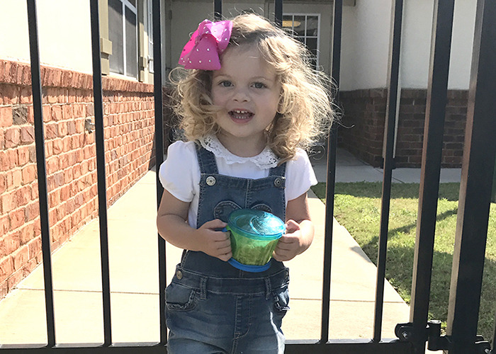 Little toddler girl smiles as she stands outside the school gates on her first day