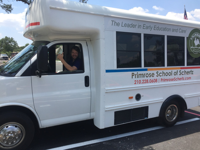 The bus driver smiles gives a thumbs up as he sits in the Primrose school bus