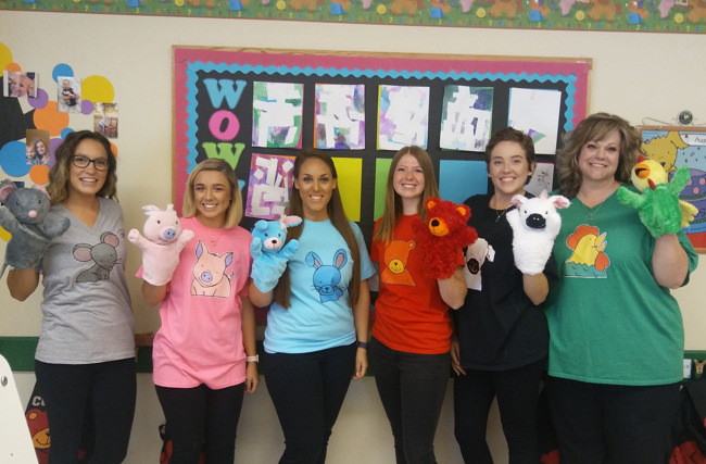 Primrose teachers celebrate twin day by wearing a Primrose puppet T shirt and posing with the same hand puppet