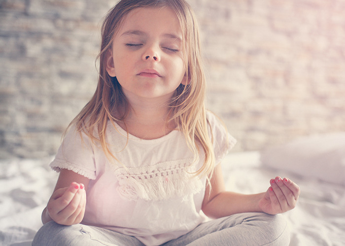 Little girl closes her eyes, sits cross legged and meditates on her bed