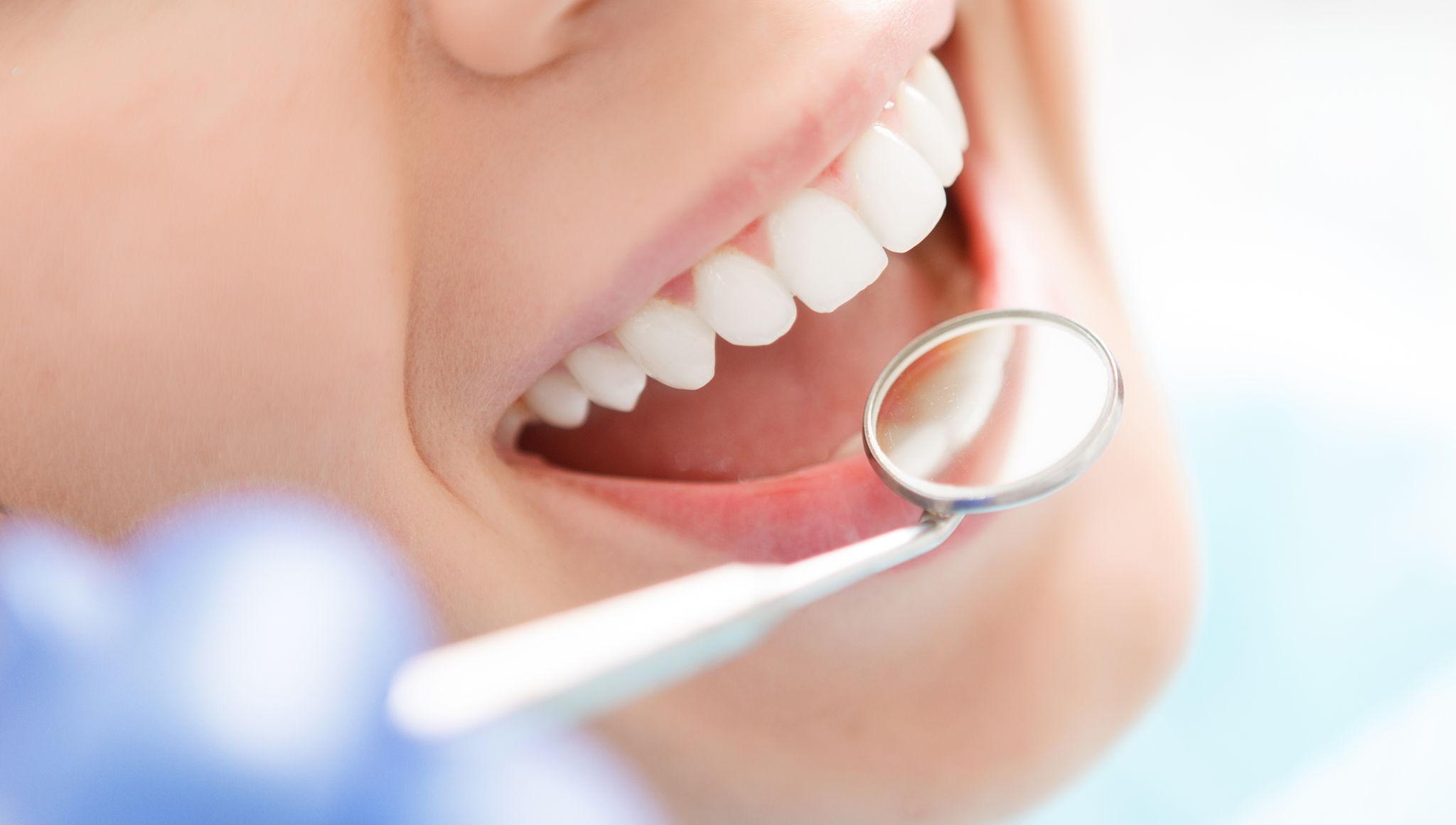 Il dentista sta esaminando i denti dopo aver usato la tecnica dell'abrasione ad aria.