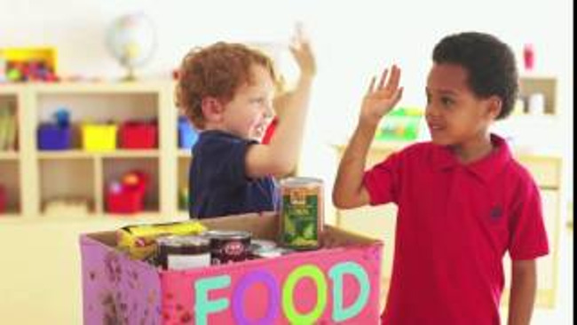 "Two young Primrose students give each other a hi five after filling the box labelled ""Food Drive"" with cans of food"