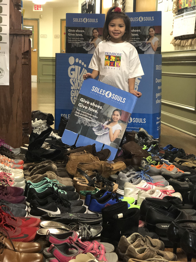 A Primrose Preschool student stands with 140 pairs of shoes!