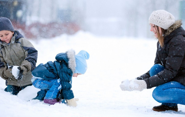 image of mom playing outside in the snow with her children