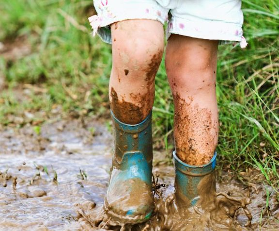 image of kid stomping in a puddle of mud