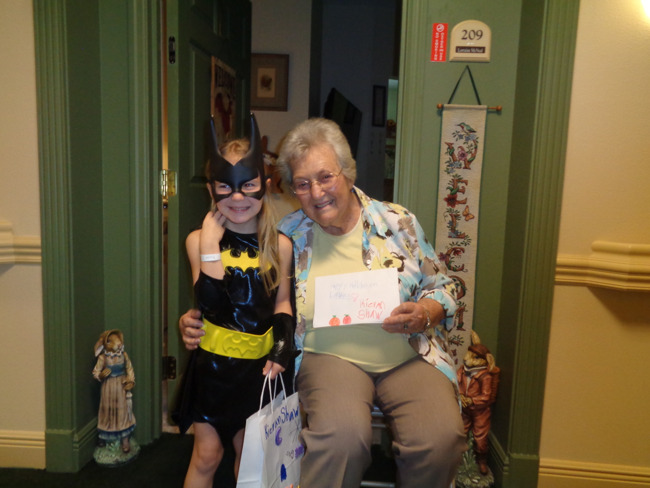 Kindergarten student Kieran, dressed as Batgirl poses with Lorraine, a senior from the Windsor