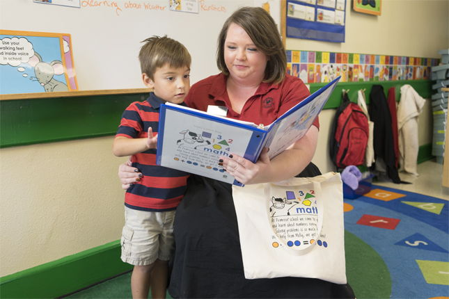 young boy reading a math book with primrose schools teacher