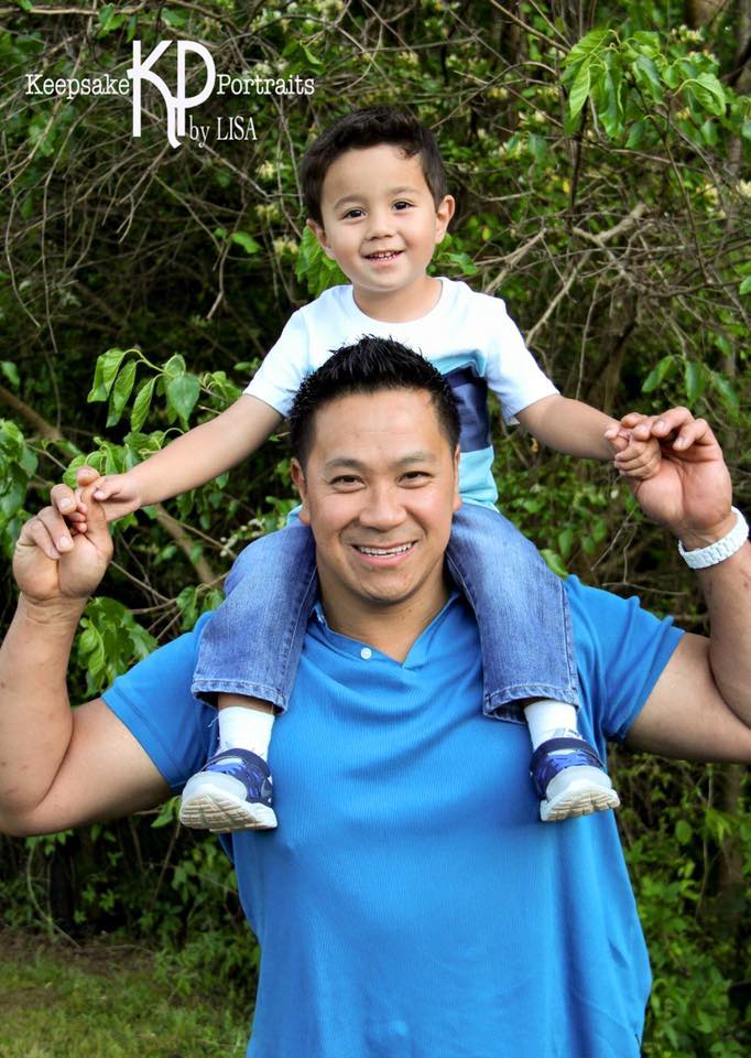 Little toddler boy sits on his father's shoulders as they both smile