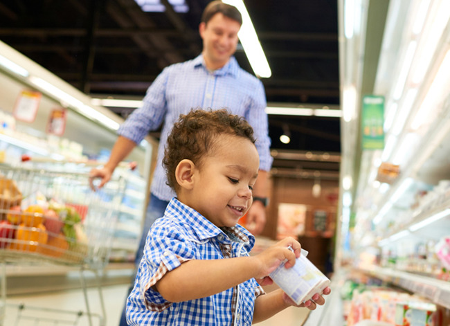 Little toddler boy picks up yogurt from a supermarket aisle while his father looks on from the back