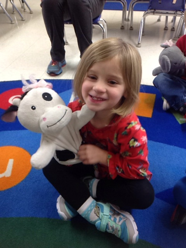 Young student smiles as she plays with Molly the cow hand puppet