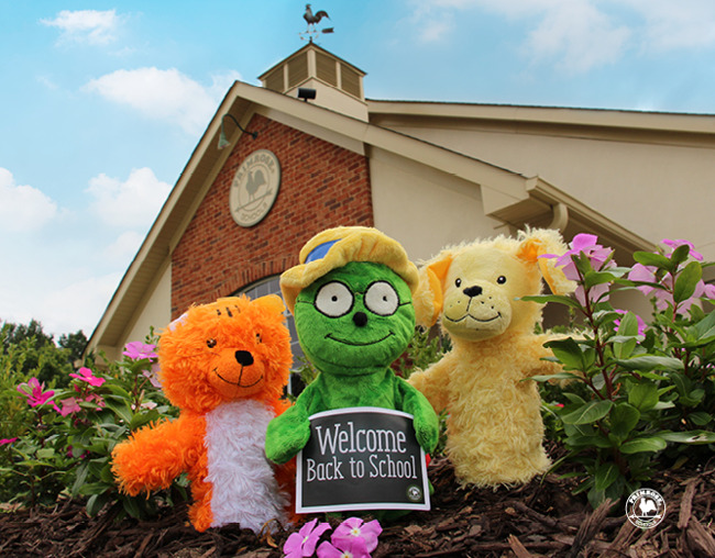 """The puppets (a cat, a bookworm, and a dog) hold a sign that says """"Welcome Back to Shcool"""" in front of a Primrose School."""