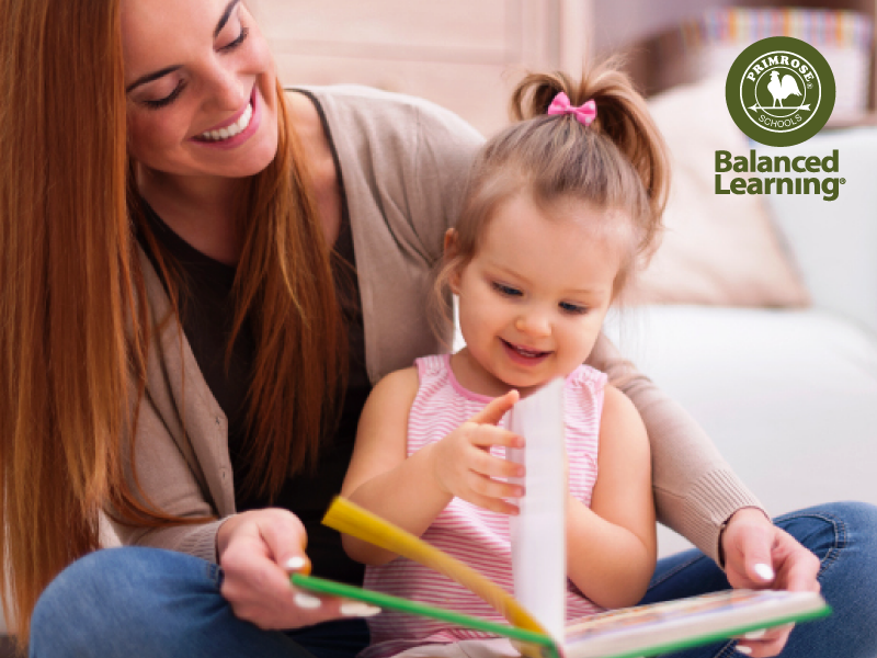 Little girl reads happily reads a book sitting on her mother's lap