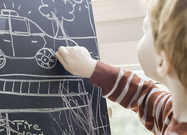 image of boy drawing a police car on a chalkboard