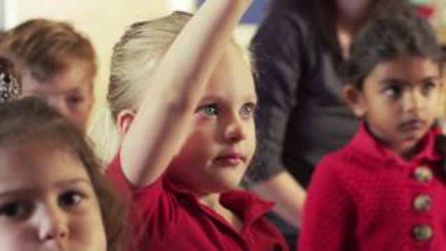 Close up of a young Primrose student raising her hand to answer a question