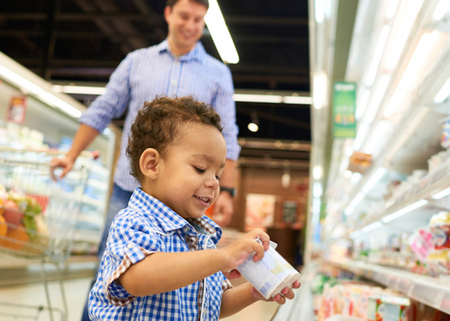 Little toddler boy picks up yogurt from a supermarket aisle as his father looks on from behind