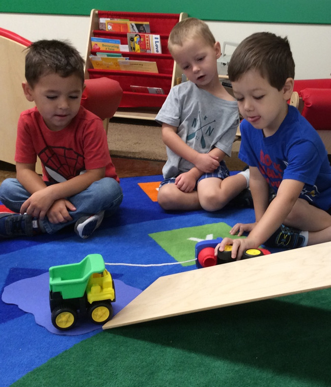 Young students play with toy trucks in a Primrose classroom