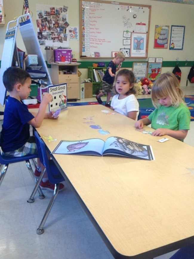 Three young Primrose students work together for a class activity