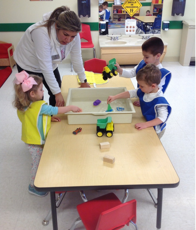 Three Primrose toddlers play with sailboats floating in a tray of water as their teacher talks to them
