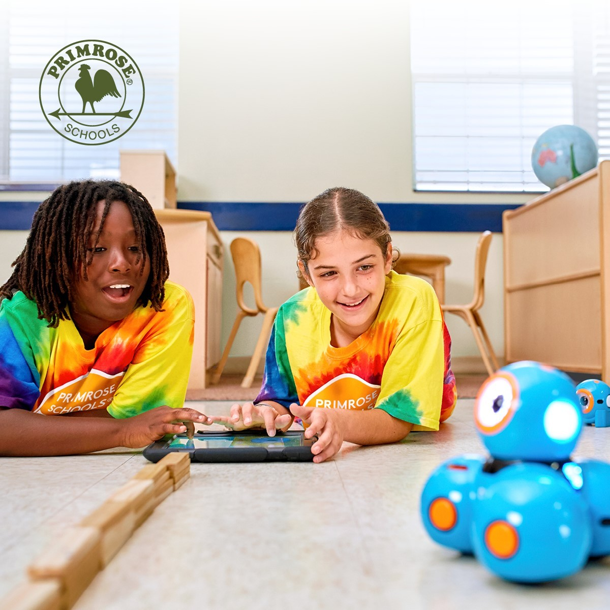 Two chidren playing with ipad and robot