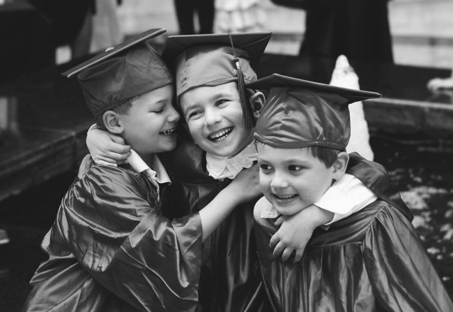 Close up of three young Primrose graduates in caps and gowns hugging each other and laughing
