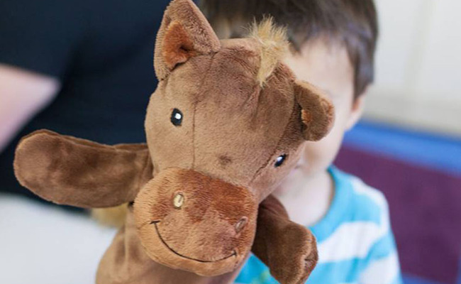 image of a little boy holding horse puppet