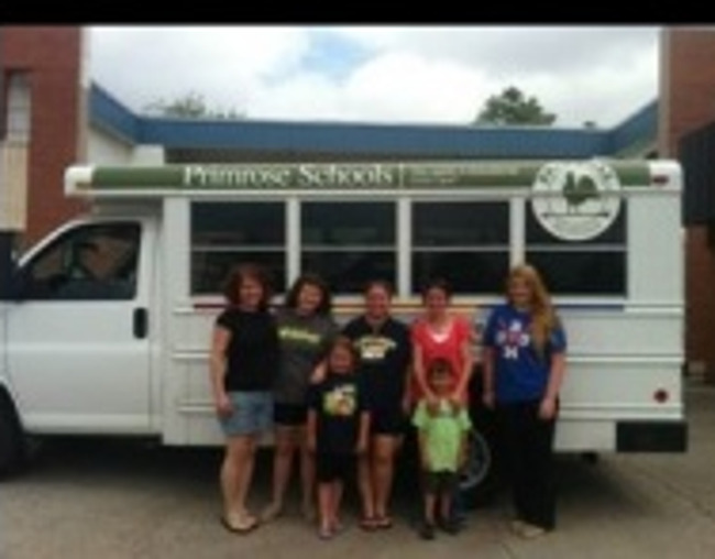 Primrose school of West Allen representatives posing with the school bus full of supplies to donate to the town of Moore, OK