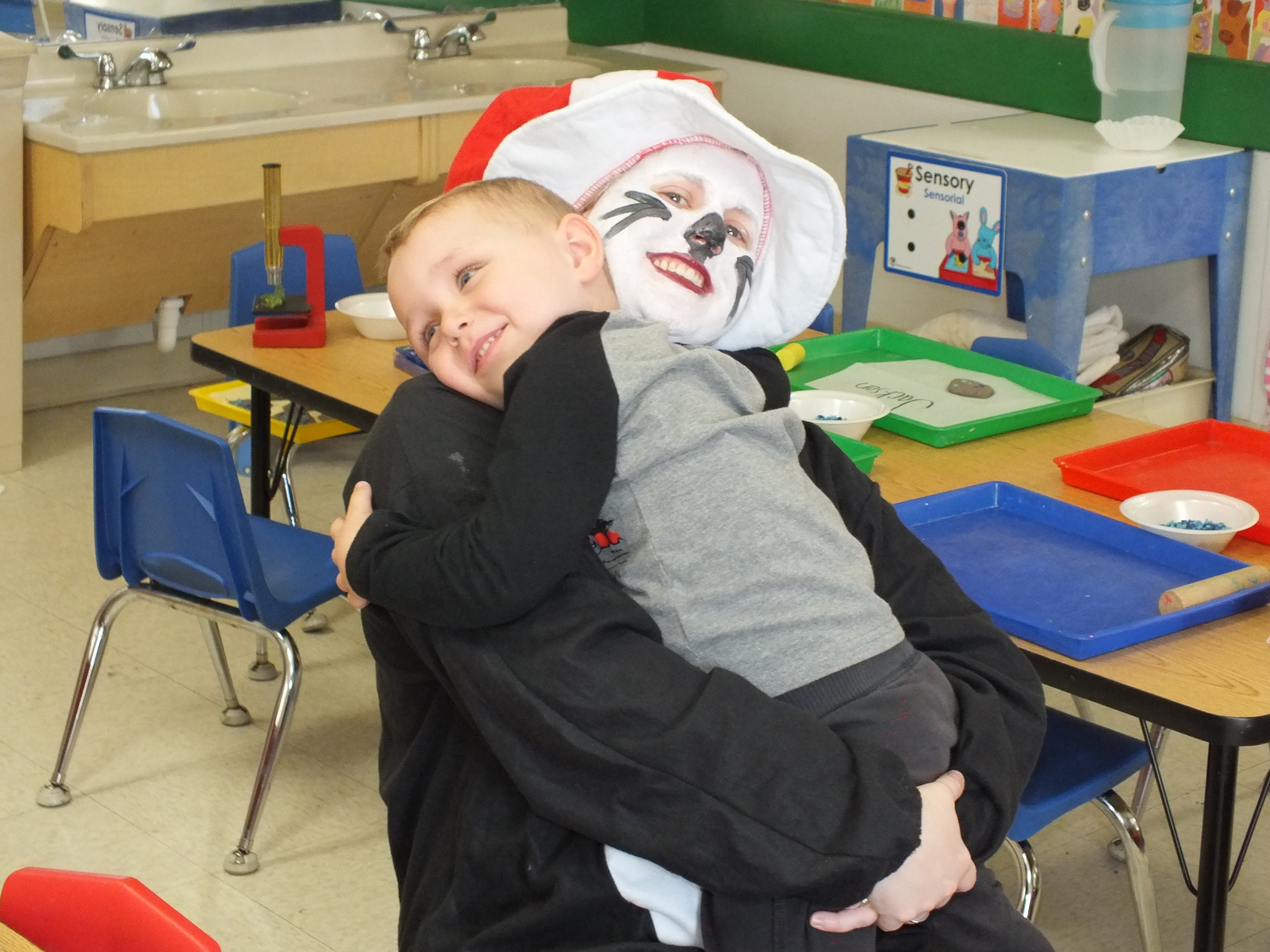 A little boy hugs a woman dressed as Dr. Seuss's Cat in the Hat