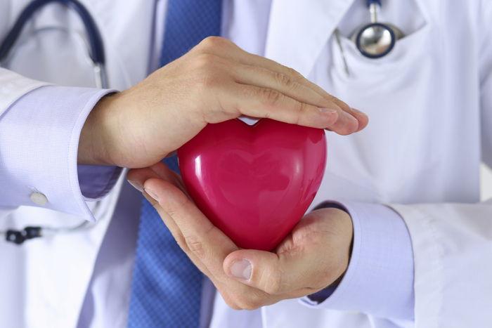 Un cardiologo stringe un cuore tra le mani, quasi a voler sottolineare l'importanza di una visita cardiologica di controllo